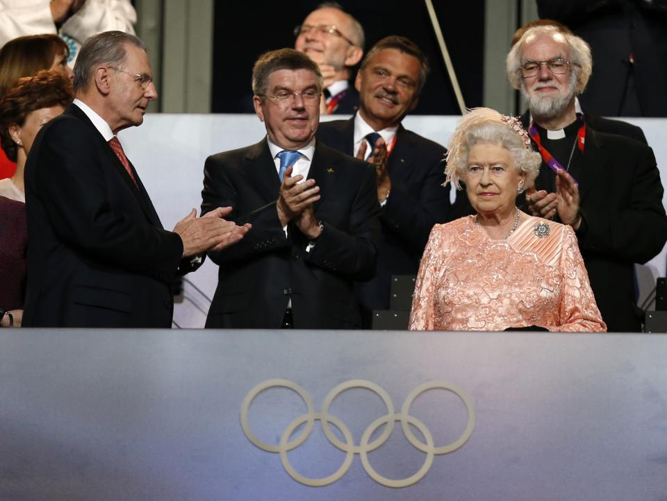 The President of the International Olympic Committee Jacques Rogge, left, and Britain's Archbishop of Canterbury Rowan Williams, back right, applaud as Britain's Queen Elizabeth II, foreground right, arrives during the Opening Ceremony at the 2012 Summer Olympics, Friday, July 27, 2012, in London. (AP Photo/Matt Dunham)