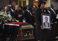 A woman holds a frame with the picture of Kenya's Internal Security Minister George Saitoti next to the casket bearing his remains on June 15, 2012 in Nairobi during a funeral mass. The helicopter crash that last year killed Saitoti and five other people was most likely caused by pilot error during bad weather conditions, a commission investigating the accident said Thursday.