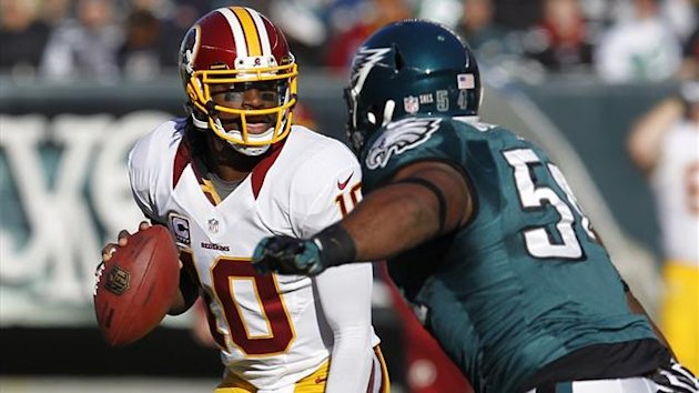 Washington Redskins quarterback Robert Griffin III looks to pass under pressure from the Philadelphia Eagles defensive end Brandon Graham