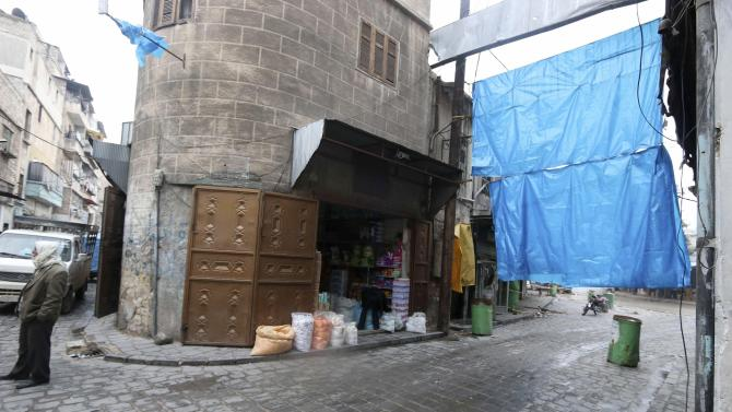 A shop owner sets up blinds outside his shop as protection from snipers loyal to Syria's President al-Assad in the old city of Aleppo
