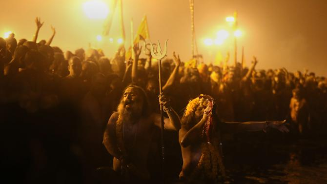 """""""Naga"""" sadhus or Hindu naked holy men shouts slogan before taking a holy dip at """"Sangam,"""" the confluence of Hindu holy rivers Ganges, Yamuna and the mythical Saraswati, during the Maha Kumbh festival at Allahabad, India, Sunday, Feb. 10, 2013. Millions of devout Hindus and thousands of Hindu holy men are expected to take a dip at Sangam on Sunday, the most auspicious day according to the alignment of stars, for the entire duration of Maha Kumbh festival, which lasts for 55 days. . (AP Photo /Manish Swarup)"""