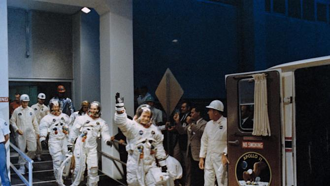 FILE - In this July 16, 1969 file photo, Neil Armstrong, waving in front, heads for the van that will take the Apollo 11 crew to the rocket for launch to the moon at Kennedy Space Center in Merritt Island, Fla. NASA renamed the historic building at Florida's Kennedy Space Center on Monday, July 21, 2014, in honor of Armstrong, the first man to step foot on the moon 45 years ago. (AP Photo/NASA, File)