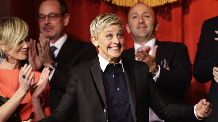 FILE - In this Oct. 22, 2012 file photo, Ellen DeGeneres reacts as she is introduced, with wife Portia de Rossi, left, before DeGeneres receives the 15th annual Mark Twain Prize for American Humor at the Kennedy Center in Washington. The talk show host is visiting Sydney and Melbourne on her six-day trip to the country for segments being filmed for her popular U.S. television show. (AP Photo/Alex Brandon, File)