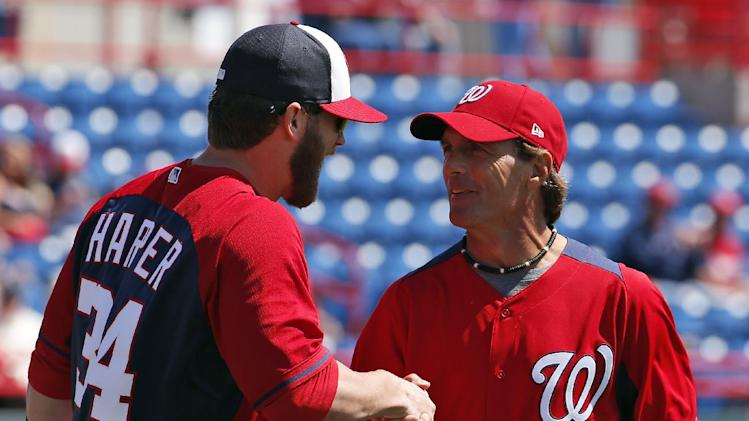 Washington Nationals left fielder Bryce Harper greets former NFL quarterback Doug Flutie, after Flutie threw out a ceremonial first pitch before a spring exhibition baseball game against the Houston Astros, Friday, March 7, 2014, in Viera, Fla