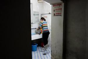 A woman in a washes up in a room beneath a building …