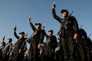 Philippine police hold up their firearms during a ceremony in Manila, on December 29, 2012. Short people hoping to join the long arm of the law in the Philippines will be left disappointed after President Benigno Aquino vetoed a bill removing height requirements for the police