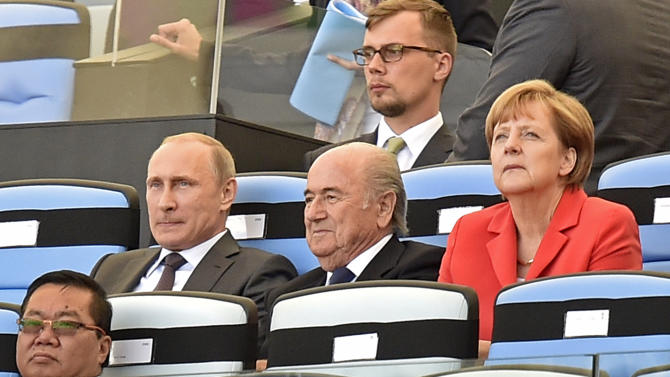 Russia's President Vladimir Putin, left, FIFA President Sepp Blatter, center, and Germany's Chancellor Angela Merkel, right, watch the opening ceremony of the World Cup final soccer match between Germany and Argentina at Maracana Stadium in Rio de Janeiro, Brazil, Sunday, July 13, 2014. (AP Photo/Martin Meissner)