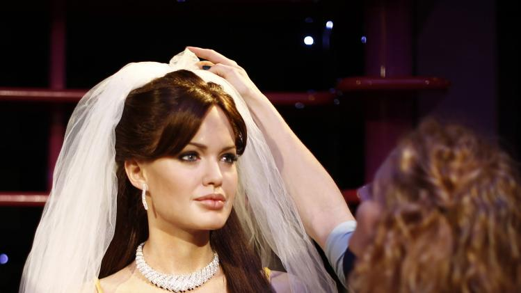 A wax model of Angelina Jolie is fitted with a bridal veil by Sydney's Madame Tussauds staffer Zoe Walton in celebration of Jolie's recent marriage to Brad Pitt