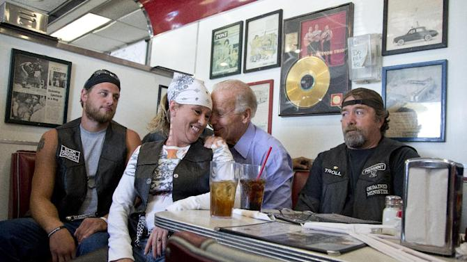 FILE - In this Sept. 9, 2012 file photo, Vice President Joe Biden talks to customers, including a woman who pulled up her chair in front of the bench Biden was sitting on, during a stop at Cruisers Diner in Seaman, Ohio. Let's be clear: the biker chick in the bandana and leather vest is NOT sitting in Biden's lap. But it sure looks like it. The vice president plunked himself down with some bikers in a diner in Seaman, Ohio, this fall, and leaned in close behind one woman, grabbing on to her shoulders as they posed for photos. That's Joe. (AP Photo/Carolyn Kaster, File)