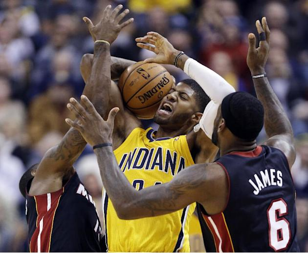 Indiana Pacers forward Paul George, center, is trapped by Miami Heat forward LeBron James, right, and guard Mario Chalmers in the first half of an NBA basketball game in Indianapolis, Tuesday, Dec. 10