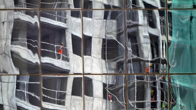 A residential building undergoing construction is reflected on the glass facades of a commercial complex in Chennai September 30, 2013. REUTERS/Babu/Files