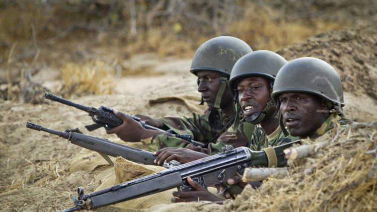 FILE - In this Monday, Feb. 20, 2012 file photo, Kenyan army soldiers stand in a dugout position at their base in Tabda, inside Somalia. Kenya's military said Friday, Sept. 28, 2012 that its troops attacked Kismayo, the last remaining port city held by al-Qaida-linked al-Shabab insurgents in Somalia, during an overnight attack involving a beach landing. (AP Photo/Ben Curtis, File)