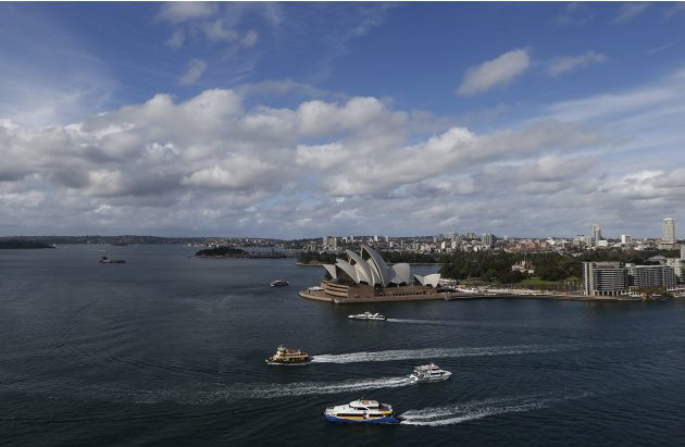 Passenger boats sail past the Sydney Opera House on a sunny winter afternoon in central Sydney