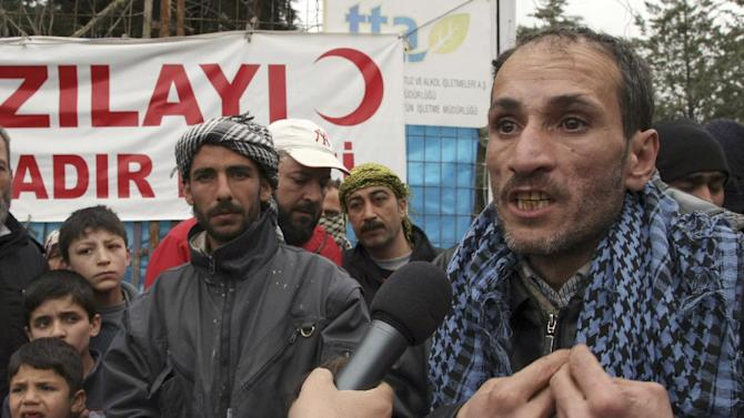 Newly arrived Syrian refugee Nizar Hajyousuf tells about horror in his Syrian hometown, Jisr Ash Shugur, as other refugees stage a protest against the Syrian regime in Yayladagi, Turkey, Monday, March 12, 2012. A Turkish official told the Associated Press there has been a marked increase in the number of refugees crossing into Turkey since the start of attacks on Idlib, saying some 1000 Syrians have fled in the past week, compared to some 1000 in one month before the violence in the northern province began. He said the number of Syrian refugees in Turkey is now 12,500.(AP Photo/Burhan Ozbilici)