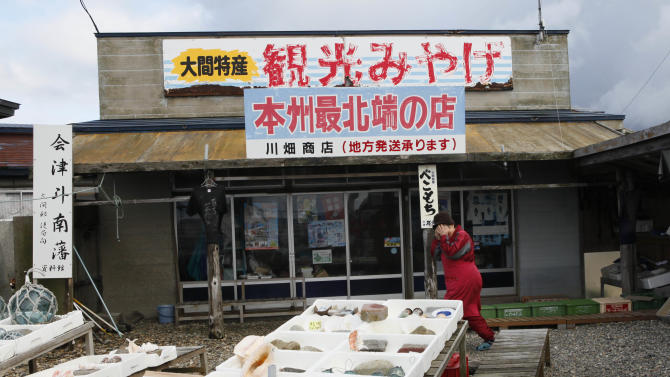In this Nov. 9, 2012 photo, a shy souvenir shop worker covers up her face as she walks by a seafood display in Oma, Aomori Prefecture, northern Japan. In nearby Oma, construction is set to resume on an advanced reactor that is not a fast-breeder but can use more plutonium than conventional reactors. Its construction, begun in 2008 for planned operation in 2014, has been suspended since the March 2011 Fukushima nuclear meltdowns, and could face further delays as Japan's new nuclear watchdog prepares new safety guidelines. The sign reads: Sightseeing Souvenirs specially from Oma. The northernmost shop in Japan's main island of Honshu. (AP Photo/Koji Sasahara)