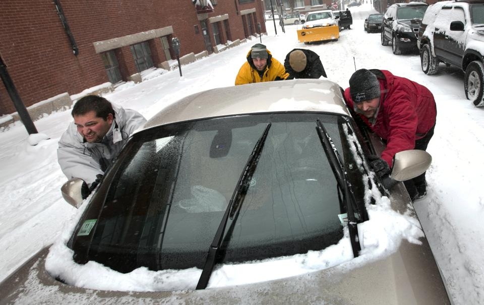 A group of men help push a sports car up a snow-covered street in the Old Port section of Portland, Maine, during a snow storm, Friday, Feb. 8, 2013. The storm is expected to dump up to two feet of snow on the region. (AP Photo/Robert F. Bukaty)