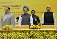 <p>Indian Prime Minister Manmohan Singh (C), flanked by Indian Chief Justice S.H. Kapadia (L) and Union Minister for Law and Justice Salman Khurshid (R), attends a legal conference in New Delhi.</p>