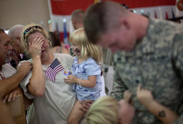 Cynthia Headrick, second from left, holding her daughter Sarienne, 5, and comforted by her husband Donald Headrick, left, all of Huntsville, Ala., cries upon seeing her son, Spc. Michael Moore, 21, ri