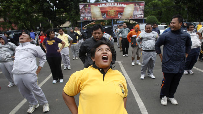 In this photo taken Dec. 4, 2012, plain-clothes Indonesian police officers do exercise during a new diet program for police in Tangerang, outskirts of Jakarta, Indonesia. Anyone over 100 kilograms (220 pounds) must follow the weight-loss program started because of the growing number of overweight officers and the perception that they are unable to provide public protection, said a Jakarta police spokesman. (AP Photo/Tatan Syuflana)