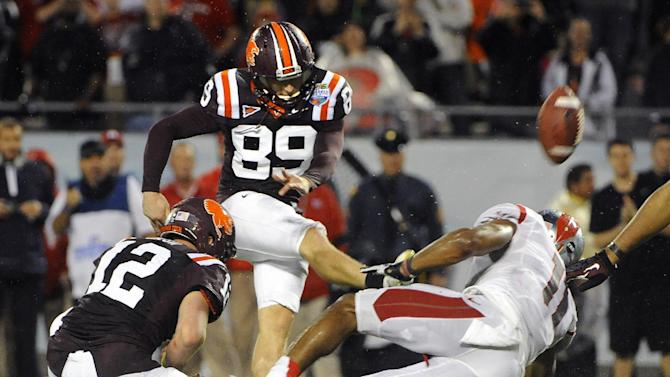 Virginia Tech kicker Cody Journell (89) gets the hold from quarterback Trey Gresh (12) while booting the go-ahead field goal in overtime in front of Rutgers defensive back Logan Ryan (11) during an NCAA college football Russell Athletic Bowl game on Friday, Dec. 28, 2012, in Orlando, Fla. (AP Photo/Brian Blanco)