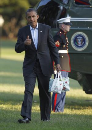 President Barack Obama gives a 'thumbs-up' as he carries bags of apples during his arrival on the South Lawn of the White House on Marine One helicopter, Saturday, Aug. 18, 2012 in Washington. Obama purchased the apples and other items in a campaign stop at Mack's Apples in Londonderry, N.H. (AP Photo/Pablo Martinez Monsivais)