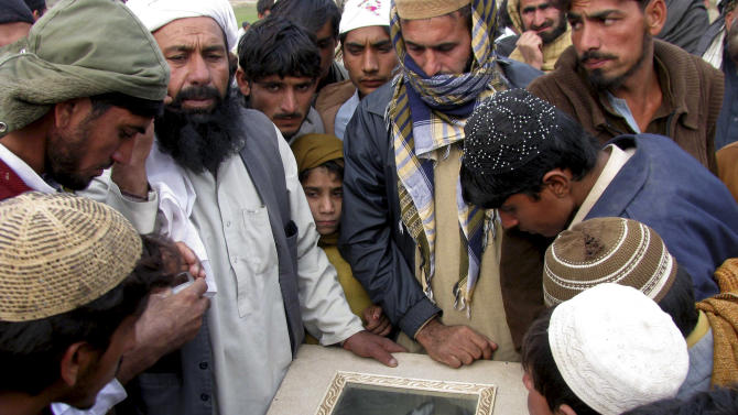 FILE - In this Wednesday, Dec. 29, 2010 file photo, villagers look at the body of a man during his funeral in Bannu, Pakistan. He was reportedly killed by a Dec. 27, 2010 U.S. drone attack in the Pakistani tribal area of Mir Ali along the Afghanistan border. American drone strikes inside Pakistan are killing far fewer civilians than many in the country are led to believe, according to a rare on-the-ground investigation by The Associated Press of 10 of the deadliest attacks in the past 18 months. (AP Photo/Ijaz Muhammad)