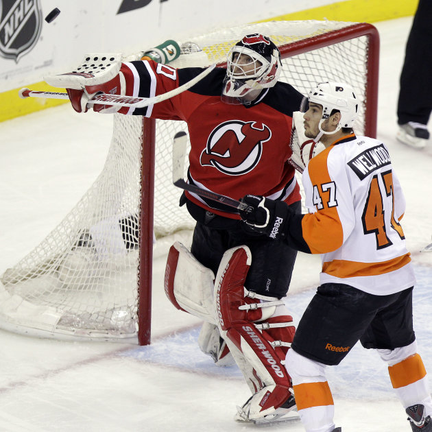 New Jersey Devils goalie Martin Brodeur, left, deflects the puck as Philadelphia Flyers' Eric Wellwood looks on during the third period of Game 4 of a second-round NHL hockey Stanley Cup playoff serie
