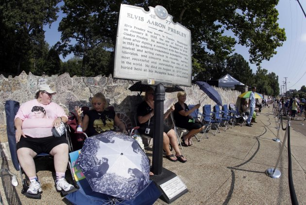 Elvis Presley fan Margaret Rabalais, left, of New Orleans, holds her spot at the head of the line outside Graceland, Presley&#39;s Memphis, Tenn. home, on Wednesday, Aug. 15, 2012. The fans are lined up to take part in the annual candlelight vigil marking the 35th anniversary of Presley&#39;s death. Rabalais has been waiting in line since 10 p.m. Tuesday night. (AP Photo/Mark Humphrey)