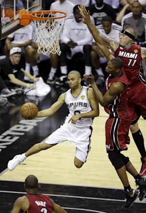 San Antonio Spurs point guard Tony Parker (9) passes the ball around Miami Heat forward Chris Andersen and center Chris Bosh (1) during the first half at Game 3 of the NBA Finals basketball series, Tuesday, June 11, 2013, in San Antonio. (AP Photo/David J. Phillip)