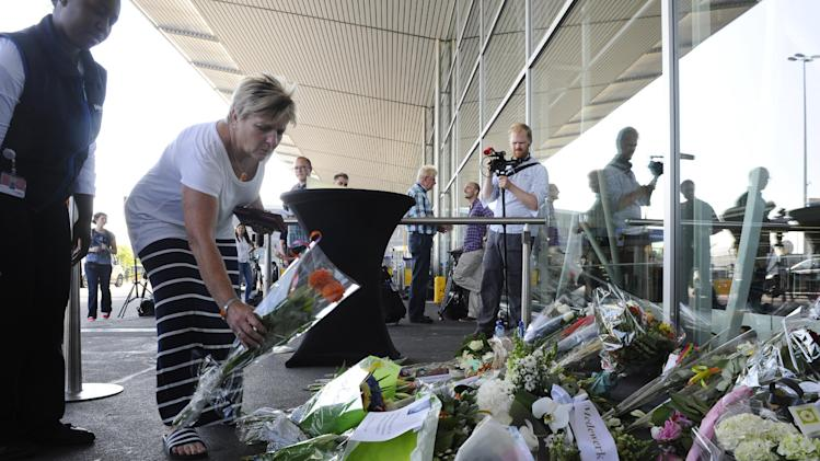 A woman lays flowers in front of Amsterdam's Schiphol airport on July 18, 2014, for those who died on flight MH17