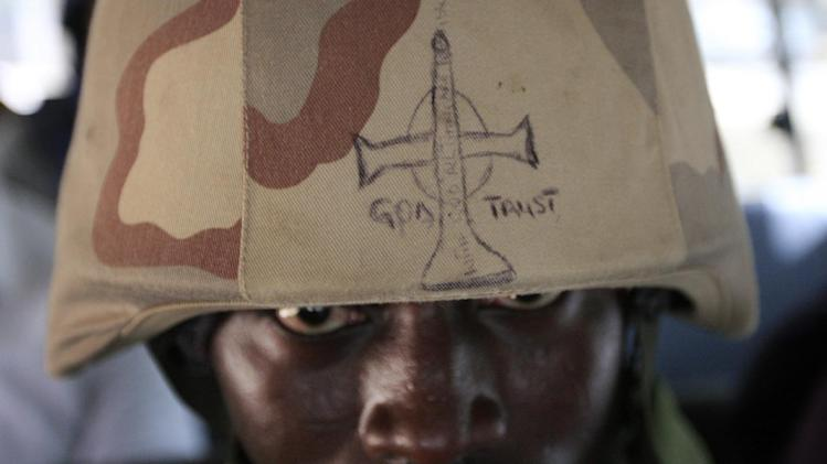 "A soldier looks out from under the brim of his helmet in Maiduguri, Nigeria, on Thursday, June 6, 2013. The writing on it reads: ""God Trust: In God All Things Are Possible"". Maiduguri is the heart of Nigeria's Islamic insurgency. Military officials took journalists on a tour there Thursday, but largely declined to give specific answers about what's happening in the country's fight against the extremists. (AP Photo/Jon Gambrell)"