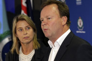 "Belinda Pulver looks at her husband William as he makes a statement regarding the arrest of a 50-year-old man, in Sydney, Australia Tuesday, Aug. 16, 2011. Paul ""Doug"" Peters was arrested on Monday and charged with breaking into Pulvers' home and chaining a fake bomb to their 18-year-old daughter Madeleine's neck, the FBI said. (AP Photo/Rob Griffith)"