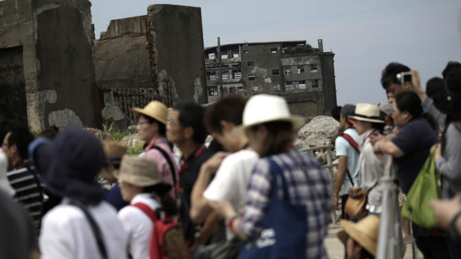 """In this June 29, 2015 photo, tourists visit Hashima Island, commonly known as Gunkanjima, which mean """"Battleship Island,"""" off Nagasaki, Nagasaki Prefecture, southern Japan. Japanese officials expressed elation Monday, July 6, 2015,  over the U.N. cultural body's approval of world heritage status for 23 historic sites illustrating the country's transformation into an industrial power at the end of the 19th century. (AP Photo/Eugene Hoshiko)"""