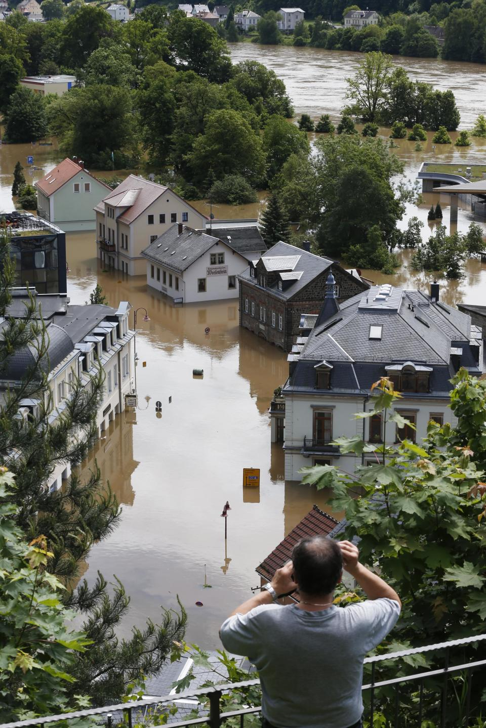A man looks  looks at  the flooded streets of the city  of Bad Schandau near the German Czech boarder in Saxony, Germany, Wednesday, June 5, 2013.  Heavy rainfalls   caused flooding in parts of Germany, Austria and Czech Republic.  (AP Photo/Markus Schreiber)