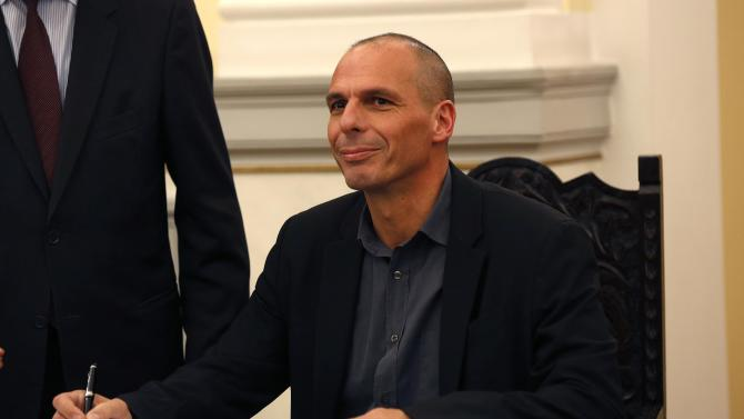 Newly appointed Greek Finance Minister Yanis Varoufakis signs official documents following a swearing in ceremony at the presidential palace in Athens
