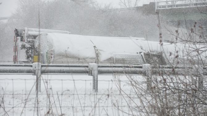 A tanker carrying hazardous chemicals is tipped on its side in the northbound lane of Interstate 57 near Champaign, Ill., closing the highway in both directions on Sunday Feb. 2, 2015. State police say a portion of Interstate 57 west of Champaign will be closed for most of Sunday as crews clean up an accident that led to a hazardous spill. Meteorologists say there's a blizzard warning in effect for the Chicago area until late Sunday. Up to 18 inches of snow are possible with up to 40 mph winds. The northern half of Illinois faces winter storm and storm warnings. (AP Photo/The News-Gazette, John Dixon)  MANDATORY CREDIT