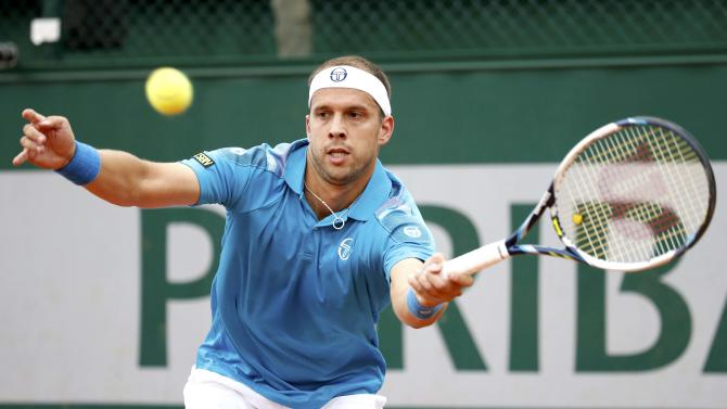 Gilles Muller of Luxembourg plays a shot to Paolo Lorenzi of Italy during their men's singles match at the French Open tennis tournament at the Roland Garros stadium in Paris