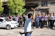A Syrian rebel fighter salutes locals chanting slogans in support of the anti-regime uprising in the Shaar district of Aleppo. Syrian rebels staved off a fightback by regime forces in Aleppo on Saturday amid growing concern about the risks of reprisals against civilians in the country&#39;s commercial capital
