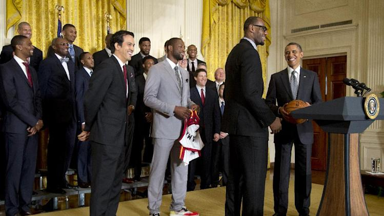 FILE - This Jan. 28, 2013 file photo, President Barack Obama stands with a signed basketball from Miami Heat forward LeBron James, second from right, forward Dwyane Wade, third from right in gray, and coach Erik Spoelstra as he welcomes the NBA basketball champion Miami Heat, to the East Room of the White House in Washington. Tall, trim and wearing catwalk clothes: Pro basketball stars have stepped up their style to become influential tastemakers. .Pro player style has been on the upswing for the past decade, especially since the NBA initiated a dress code in 2005, according to observers. (AP Photo/Carolyn Kaster, file)