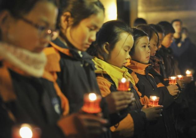 Pupils hold candles during a ceremony marking 76th anniversary of Nanjing massacre at Nanjing Massacre Museum in Nanjing
