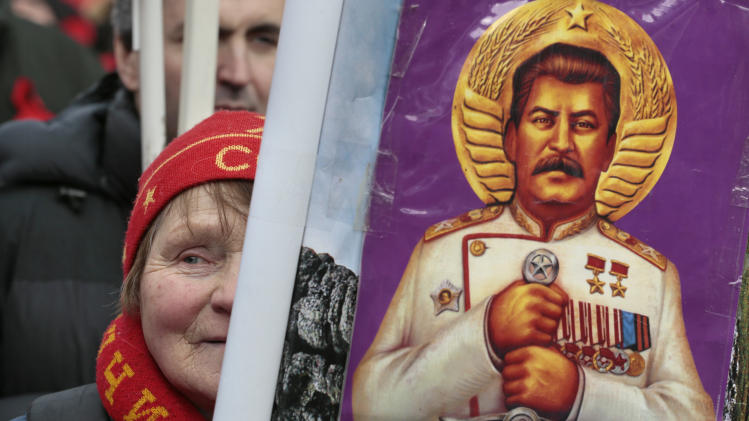 FILE - In this Saturday, Feb. 23, 2013 file photo a woman holds a portrait of Soviet dictator Josef Stalin during a communist rally marking the Defenders of the Fatherland Day in Moscow, Russia. An opinion survey commissioned by the Carnegie Endowment has revealed that Soviet dictator Josef Stalin has remained widely admired in Russia and other ex-Soviet nations despite his repressions that killed millions of people. It has found that support for Stalin in Russia has actually increased since the 1991 collapse of the Soviet Union. (AP Photo/Mikhail Metzel)