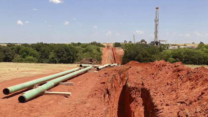 In this Friday, July 20, 2012 photo, pipe for a pipeline is readied for installation near a drilling rig, near Calumet, Okla. Oklahoma is one of several states, including North and South Dakota, that has enjoyed a boom in the energy sector driven in large part by new and improved drilling techniques such as horizontal drilling and hydraulic fracturing, which cracks open fissures in rock formations to retrieve oil and gas. (AP Photo/Sue Ogrocki)