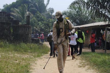 A health worker disinfects a road in the Paynesville neighborhood of Monrovia