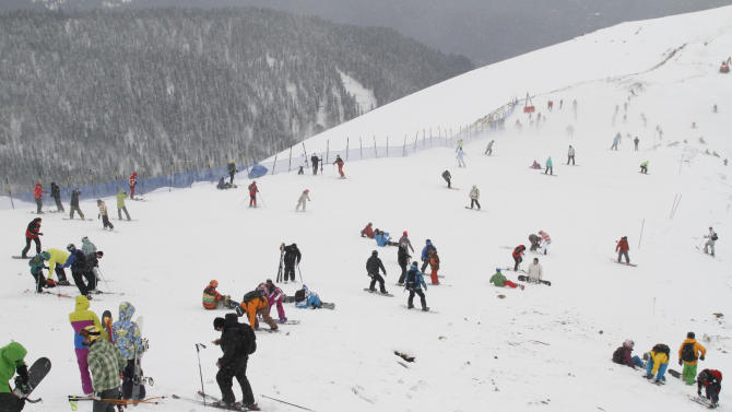 FOR STORY RUSSIA SOCHI YEAR TO GO - In this photo dated Saturday, Dec. 24, 2011, people enjoy snow at a ski resort in Krasnaya Polyana near the Black Sea resort of Sochi, southern Russia.  With just one year till the opening ceremony of the winter Olympic 2014 Sochi Games, the Black Sea resort of Sochi is a vast construction site sprawling for nearly 40 kilometers (25 miles) along the coast and 50 kilometers (30 miles) up into the mountains, with no escape from the clang and clatter of the construction works, the drilling, jack-hammering and mixing of cement. (AP Photo/Igor Yakunin)
