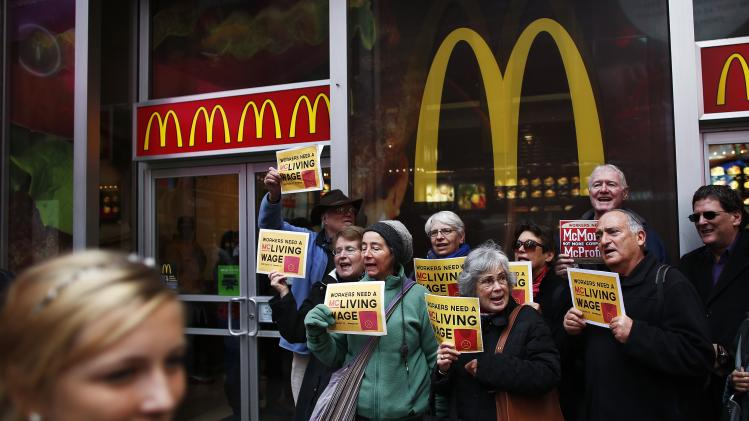 "Members of ""MoveOn"" shout slogans against McDonald's outside one of its restaurants in Times Square, New York"