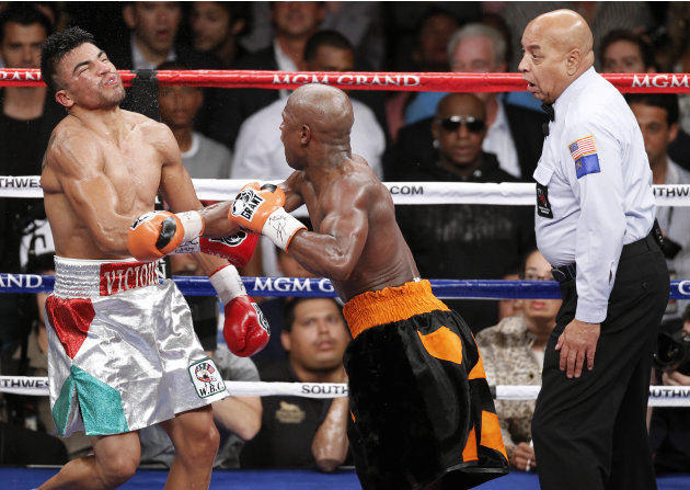 Floyd Mayweather, center, delivers a knockout punch to Victor Ortiz as referee Joe Cortez, right, looks on in the fourth round during a WBC welterweight title fight, Saturday, Sept. 17, 2011, in Las V