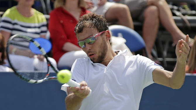 Jerzy Janowicz, of Poland, returns a shot against Lukas Rosol, of Czech Republic, in the championship match of the Winston-Salem Open tennis tournament in Winston-Salem, N.C., Saturday, Aug. 23, 2014. Rosol won 3-6, 7-6 (3), 7-5. (AP Photo/Chuck Burton)