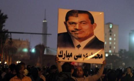 A protester in Cairo holds up a poster with the faces of current Egyptian President Mohamed Morsi and former President Hosni Mubarak as public anger mounts that Morsi is seizing too much power.