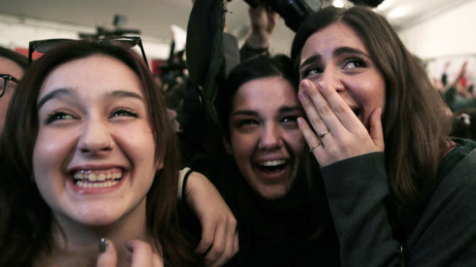 Supporters of left-wing Syriza party react as they watch the exit poll results at an election kiosk in Athens, Sunday, Jan. 25, 2015. A Greek state TV exit poll was projecting that anti-bailout party Syriza had won Sunday's parliamentary elections _ in a historic first for a radical left wing party in Greece. (AP Photo/Lefteris Pitarakis)