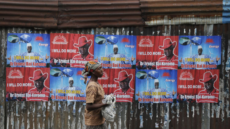 A woman walks past campaign posters for incumbent President Ernest Bai Koroma, in central Freetown, Sierra Leone Thursday, Nov. 15, 2012. Ten years after the end of a devastating civil war, Sierra Leone will go to the polls on Saturday to choose between incumbent Koroma and opposition leader Julius Maada Bio. (AP Photo/Rebecca Blackwell)